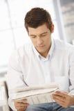年轻人读取报纸 图库摄影