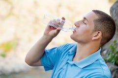 年轻人饮用水 库存照片