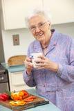 年长妇女饮用的茶在厨房里 免版税图库摄影