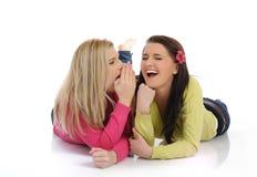 说闲话的女孩相当二个年轻人 免版税图库摄影