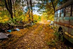 Ônibus escolar e carros destruídos em um cemitério de automóveis Fotografia de Stock Royalty Free