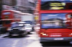 Ônibus vermelhos e táxis pretos na estrada no borrão de movimento de Londres Imagens de Stock Royalty Free
