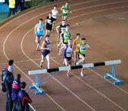 000 2个男孩m种族未认出运行的跳栏板 免版税库存照片