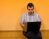 02他的膝上型计算机人工作年轻人 免版税库存图片