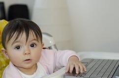1个女婴她的对尝试的使用年的netbook 免版税库存照片