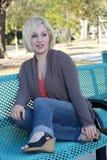 1个美丽的长凳白肤金发的偶然公园 库存图片
