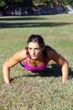 1 красивейшее брюнет делает outdoors pushups Стоковые Изображения