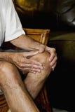 1 человек колена массажируя боль Стоковая Фотография