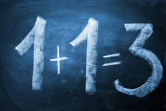 1+1=3. Wrong sum 1 +1 = 3 written on the blackboard Stock Images