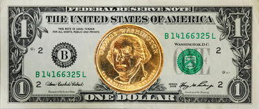 The $1 dollar bill with the dollar coin on the top. The United States $1 dollar bill with the George Washington dollar coin on the top Royalty Free Stock Image