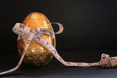 1 Easter Egg, Diets and Tape Measure. Image of one easter egg with a tape measure wrapped around it, conceptual dieting - room left on image for text royalty free stock photos