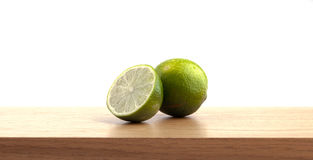 1 and a half lime on wooden plank. Stock Photos