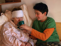 1 pojke matar den sjuka kvinnan Royaltyfri Bild