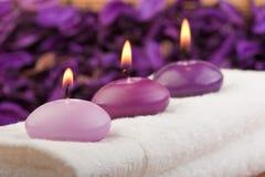 1 stearinljus masserar den purpura handduken Fotografering för Bildbyråer