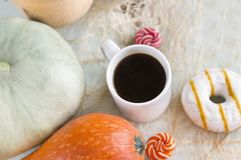 1 white coffee mug among the pumpkins, donut with icing, candy c Royalty Free Stock Photos