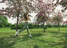 Free 1 White Woman With Long Hair In Sports Leggings And A Top, Sneakers, A Girl Running Through A Spring Blooming Apple Orchard Stock Images - 169066424