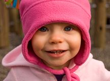 1 Year Old Girl in Bright Pink Hat. 1 year old girl happy and content smiling while wearing a bright pink hat outside Stock Images