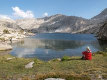 10,568' Sierra Nevada Lake. A hiker overlooks 10,568' Three Island Lake in the John Muir Wilderness of the Sierra National Forest Stock Image