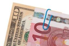 10 billetes de banco euro y de 10 dólares sujetados Foto de archivo libre de regalías
