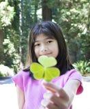 10 Einjahresmädchen, das den Klee mit drei Blättern anhält Stockfotos