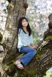 10 Einjahresmädchen, das im Kirschbaum sitzt Lizenzfreie Stockfotografie