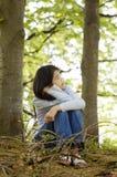 10 Einjahresmädchen, das ruhig im Holz sitzt Stockbilder