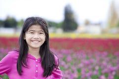 10 Einjahresmädchen, das vor Tulpefeldern lächelt Stockfotos