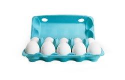 10 weiße Eier in einem Kartonkasten. Stockbilder