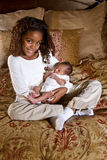 10 year old girl holding newborn sibling Royalty Free Stock Image