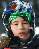 A 10 years old with a ski helmet. An multi ethnic boy  with a serious look gets ready to ski Royalty Free Stock Photography