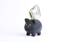 Черная копилка с 100 долларами счета падая в шлиц на белой предпосылке студии Стоковые Изображения