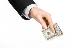 金钱和企业题目:在拿着100美元的钞票在白色的一套黑衣服的手在演播室隔绝了背景 库存图片