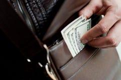 100 billetes de dólar y un bolso de cuero Fotografía de archivo