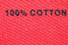 100% cotton - picture label on clothes. Close-up. 100% cotton - picture label on red clothes. Close-up Royalty Free Stock Photography