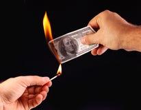 $ 100 in der Hand, legte Feuer auf eine Abgleichung. Stockfotos
