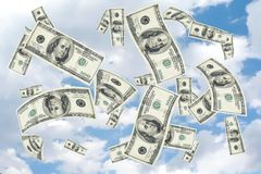 100 dollar bill shower. Concept image with copy and cropping space depicting a money shower of 100 hundred dollar bills falling from a cloudy blue sky Stock Photos