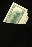 100 dollar bills stick out of the pocket. Of black jeans Stock Photos