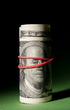 100 Dollar roll tightened with red rubber band. Stock Image