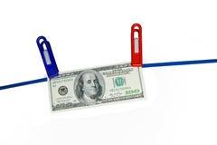 100 Dollarbanknote, die an einem Seil hängt Stockfoto
