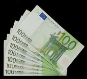 100 Euro Bills - Money. 100 euro notes on a black isolated background Stock Image