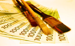 100 Euro with brushes. 100 Euro notes on a white background with three brushes Stock Photo