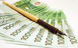 100 Euro with old pen. 100 Euro notes on a white background with old pen Stock Image