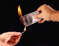 $ 100 in hand, set fire to a match. Stock Photos
