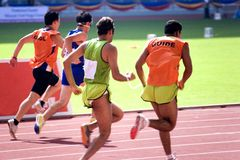 100 Meters for Blind Persons. Blind athletes (with guides) competing in a Men's 100 meters race stock photo