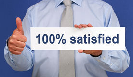 100% satisfied sign. Body of businessman with thumb up holding 100% satisfied sign Royalty Free Stock Photos
