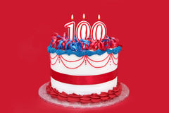 100th Cake. With numeral candles, on vibrant red background Royalty Free Stock Image