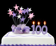 100th Cake. Fancy cake with number 100 candles.  Decorated with ribbons and star-shapes in pastel tones against black background Royalty Free Stock Images