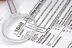 1040 Steuerformular und ein Vergrößerungsglas Stockbilder