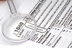1040 tax form and a magnifying glass Stock Images