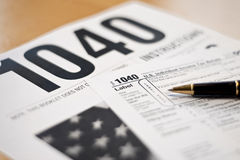 1040 Tax Prep. Close up view of American tax forms with ball point pen Royalty Free Stock Photography